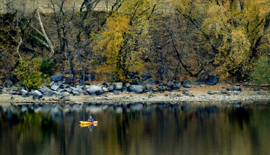 Late fall colors surround an angler on the Mississippi River in St. Cloud in this file photo.