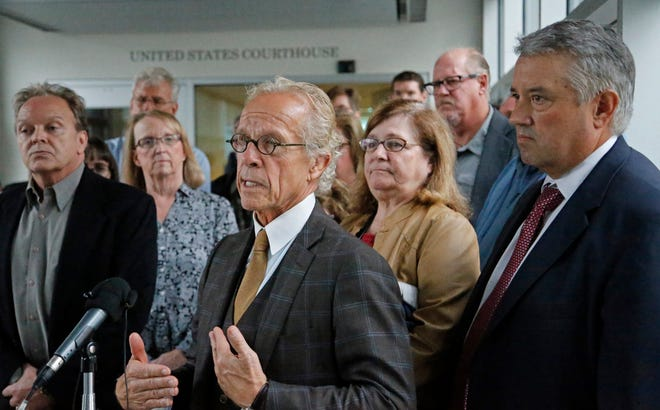 Attorney for clergy abuse survivors Jeff Anderson stands in front of survivors after a U.S. Bankruptcy Court approved a settlement that includes $210 million for victims of clergy sex abuse, Tuesday, Sept. 25, 2018, in Minneapolis.