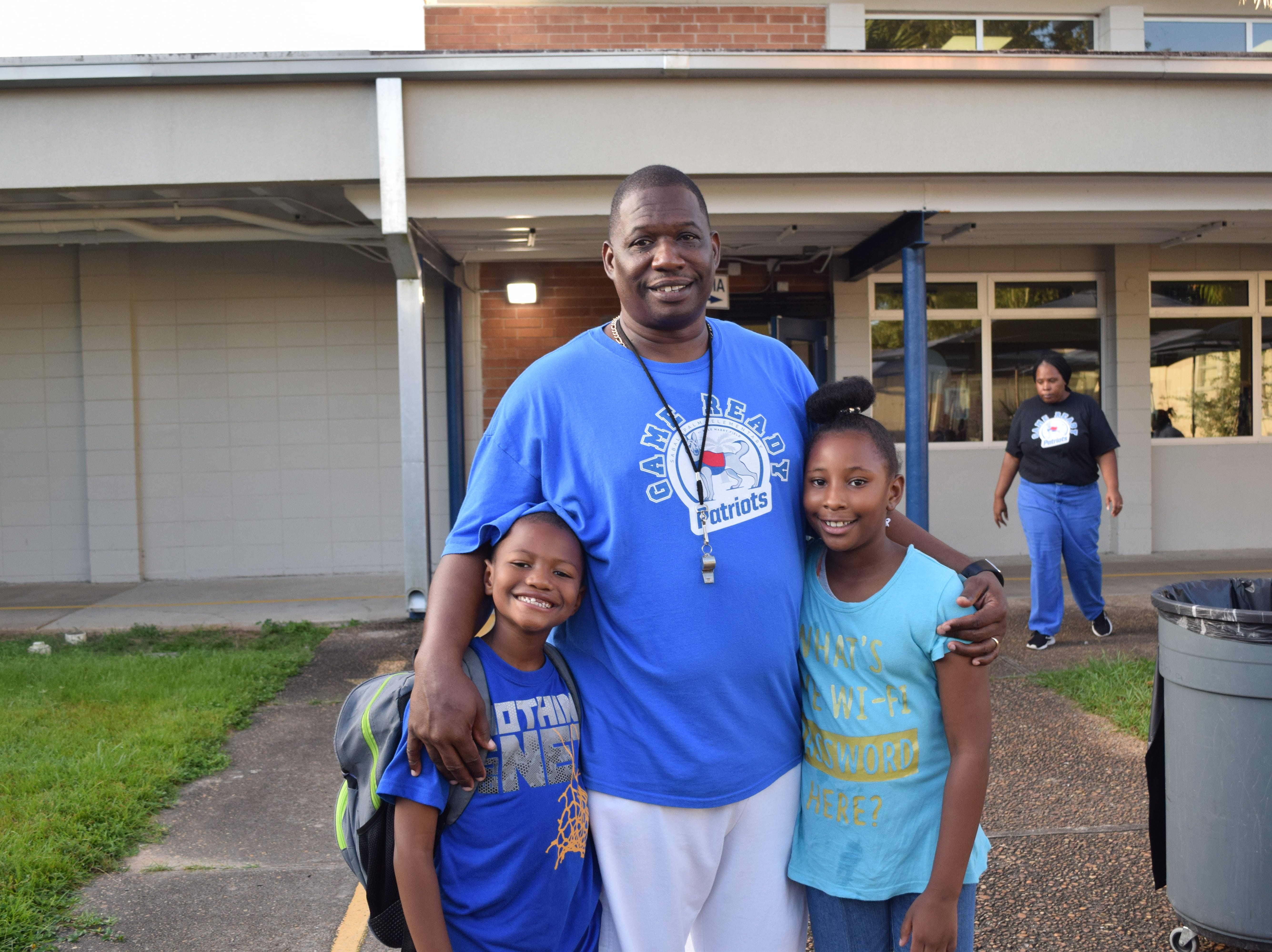 "Ronald Hollis (center) is a volunteer at Sabal Palm Elementary School where his children, Ronald ""RJ"" Hollis Jr. and Rondasha Hollis, attend. He came to school Wednesday morning as part of the doughnuts for dads event."