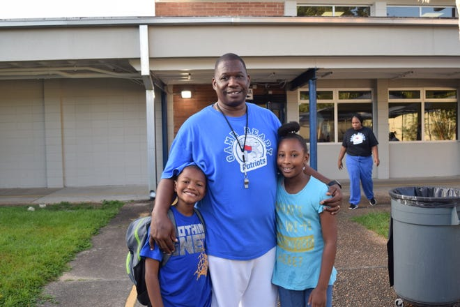 """Ronald Hollis (center) is a volunteer at Sabal Palm Elementary School where his children, Ronald """"RJ"""" Hollis Jr. and Rondasha Hollis, attend. He came to school Wednesday morning as part of the doughnuts for dads event."""