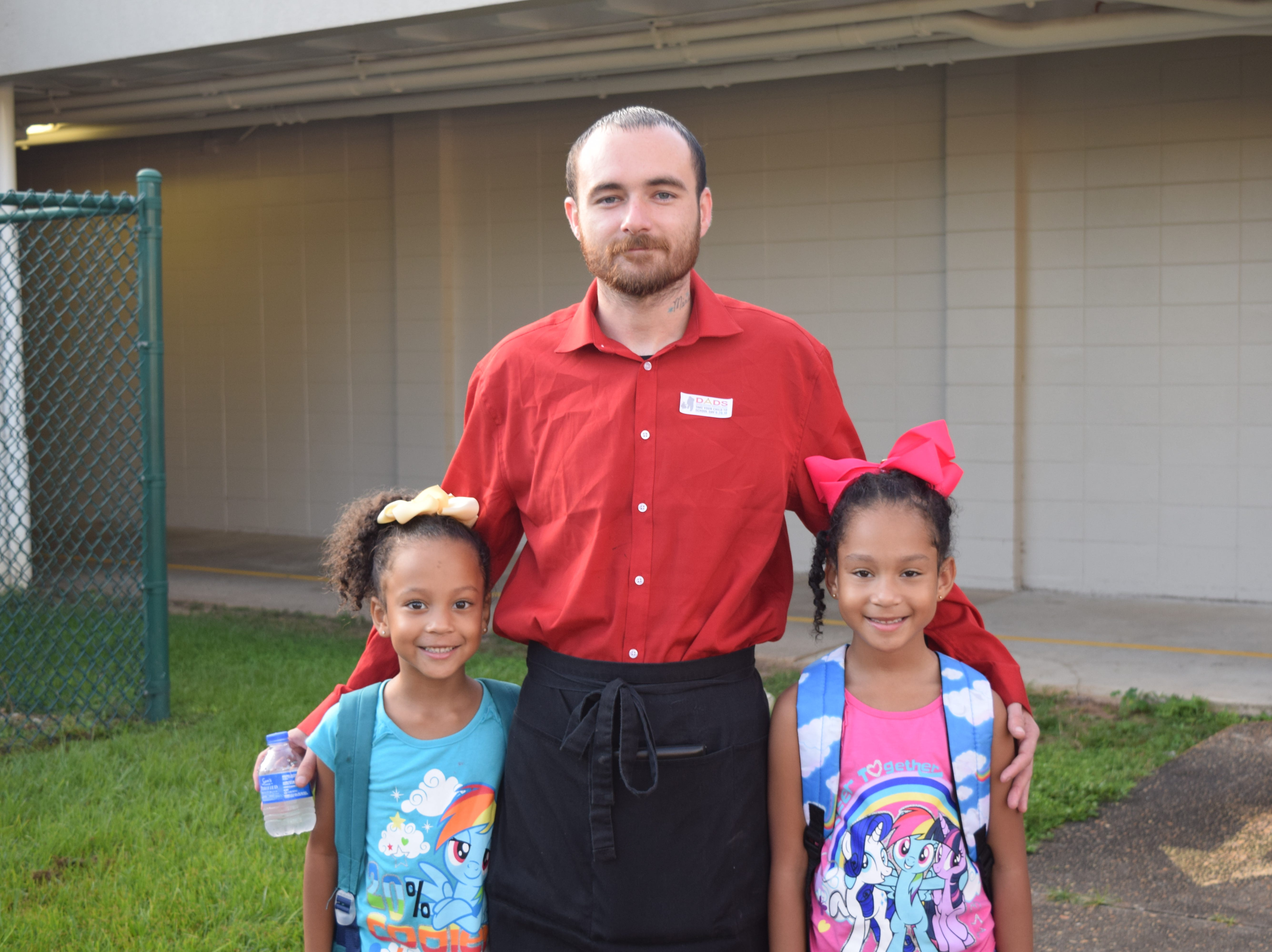 Joey Davis (center) brought his daughters Kaylee (left) and Kelsey Gaskins, both in Kindergarten, to Sabal Palm Elementary School Wednesday during doughnuts for dads.