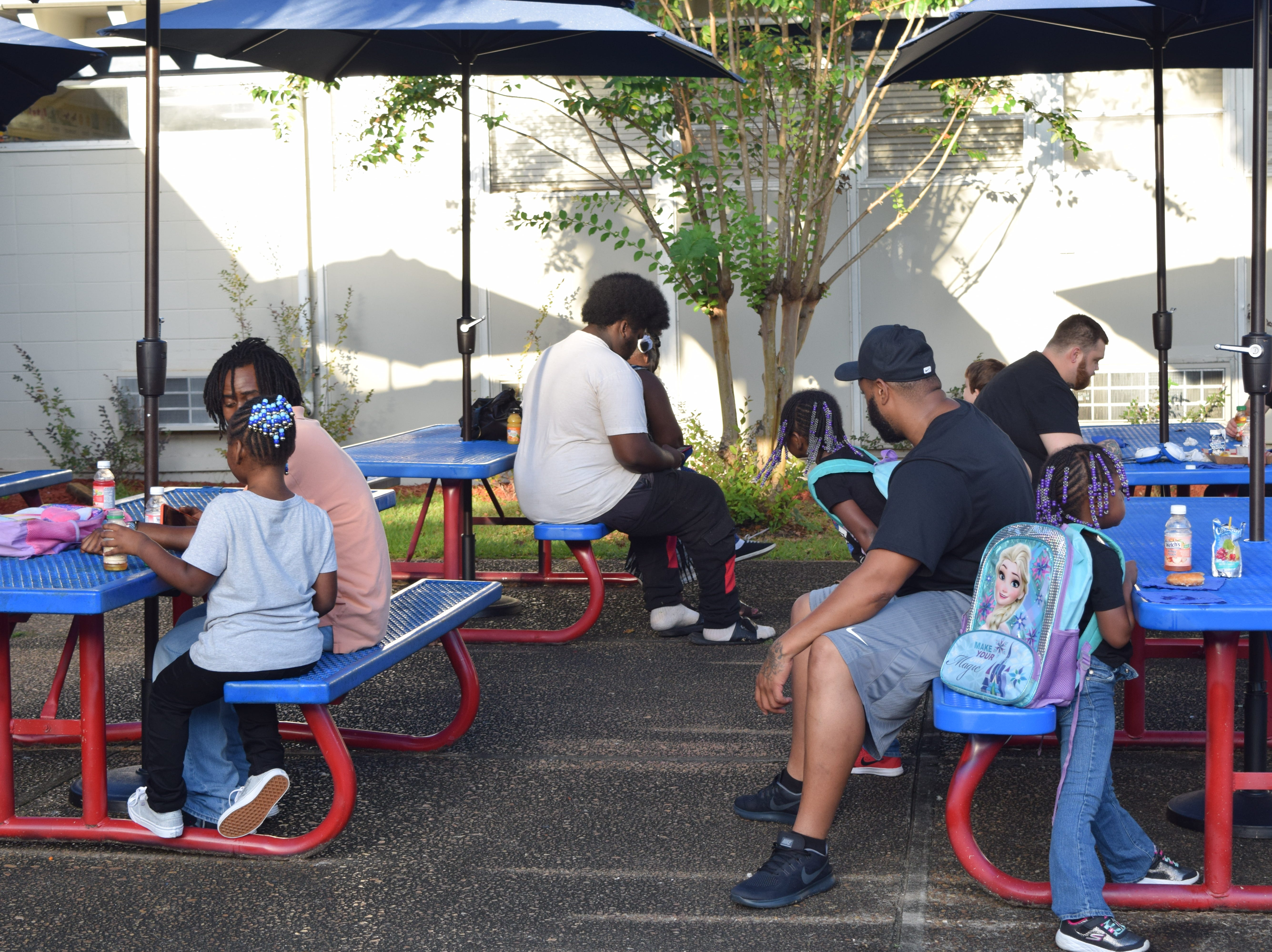 Dads sit with the children before school, eat doughnuts and drink juice for the doughnuts for dads event at Sabal Palm Elementary School.