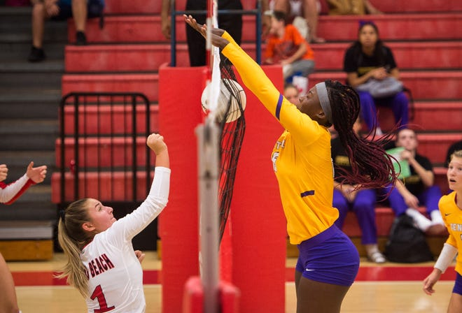 Fort Pierce Central's Brianna Jackson (right) hovers over the top of the net to defend against Vero Beach's Lily Stirrat, who tries in vain to bump the ball over, during the third game of the high school volleyball match Tuesday, Sept. 25, 2018, at Vero Beach High School.