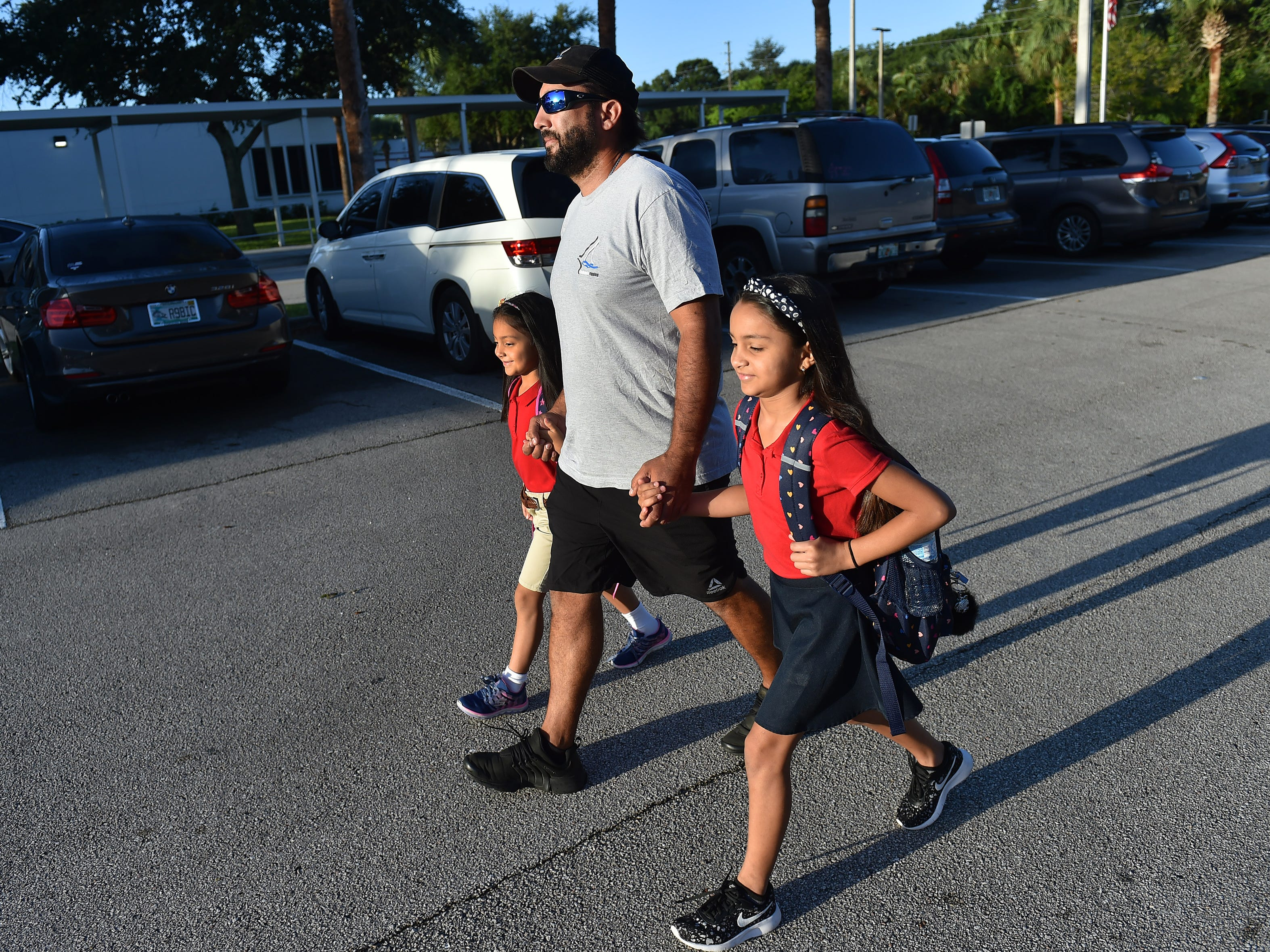 """I think it's a really cool thing,"" said Arturo Lopez, of Fort Pierce, while escorting his children Sadie, 6, (left) and Alexie, 9, into Fairlawn Elementary School, and to their first and fourth grade classrooms, for 'Take your dad to school day' on Wednesday, Sept. 26, 2018, in Fort Pierce. ""The school is different from others, and I think this is something different, really nice, and it's a really cool experience to have with your kids."" Dozens of fathers lined up with their children outside the school to walk their kids to their classrooms, meet teachers, and sign a contract promising their commitment to their children's education. ""It's always a great thing when we can bring families together with what we're doing in education,"" said Kevin Perry, Principal at Fairlawn Elementary. ""And this just gives us another opportunity to specifically invite dads to be a part of the educational process."" CQ: Arturo, Sadie,and Alexie Lopez, Kevin Perry"