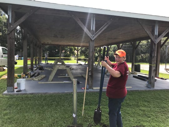 United Way Day of Caring volunteer Cathy Shain digs a post hole at Grace Grove Community Park.