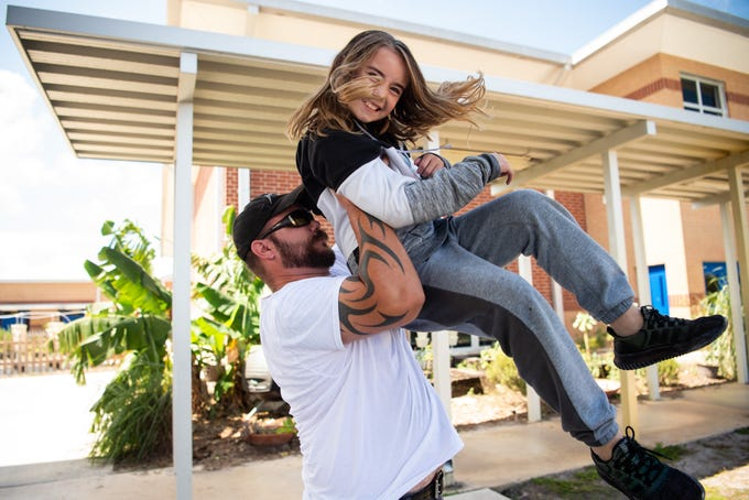 "J. D. Parker School of Science, Math and Technology third-grader Alincia Karr, 9, is hoisted by her father, Albert Karr, both of Stuart, as they spend time together during recess for the school's ""Dudes Day"" event, coinciding with the Florida Department of Education's ""Dads Take Your Child to School Day,"" on Wednesday in East Stuart. ""I took today off...I thought it'd just be fun to do,"" Albert Karr said. ""She's real good with math and science, same as me, I help her with her homework every night."" He added that it was also Alincia's first day of chorus. ""I always hear her singing when she thinks I'm not paying attention."""