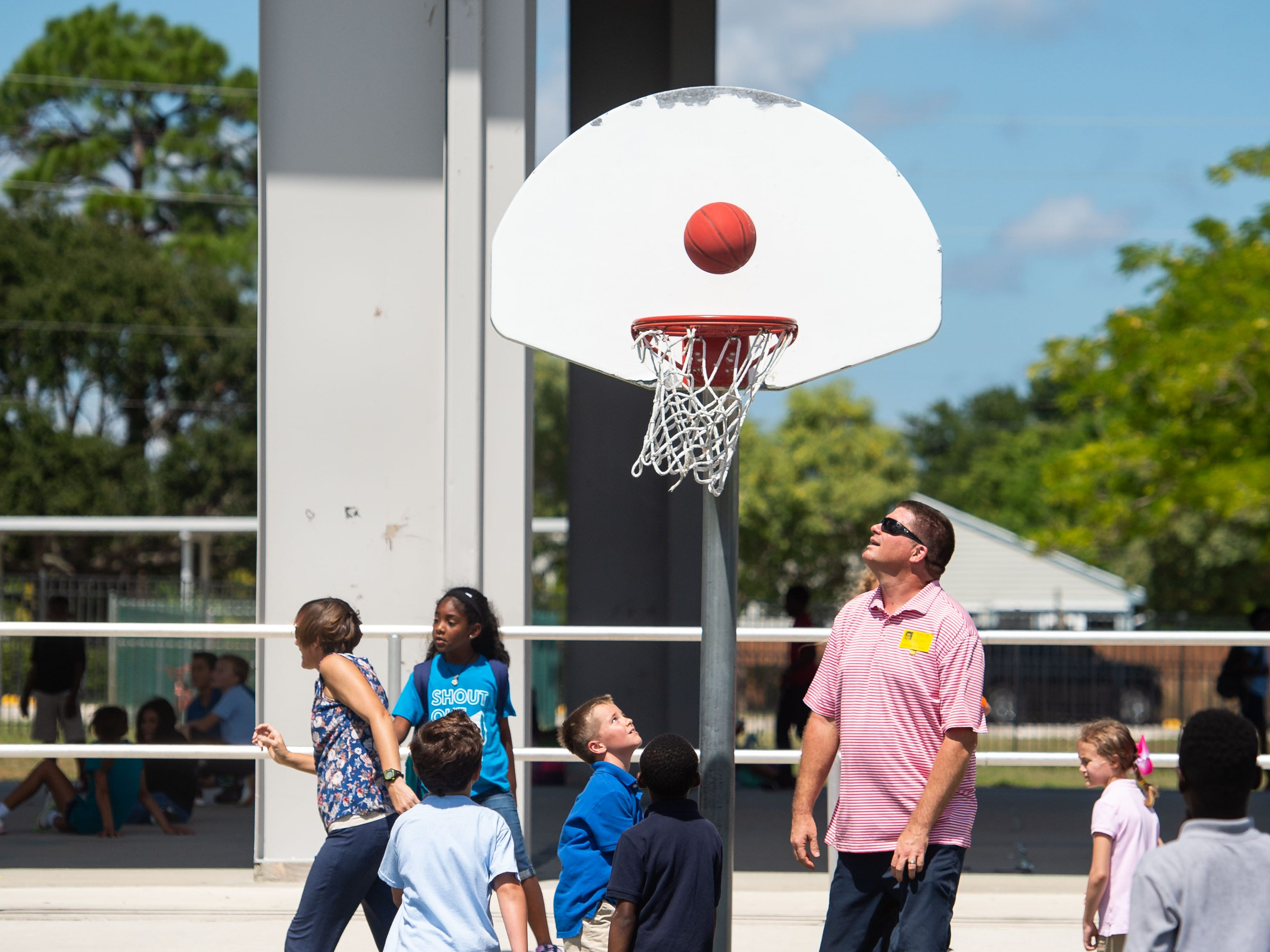 "Justin Flaitz (right), of Stuart, waits for a rebound as he plays basketball during recess with his son, Cooper Flaitz, 8, and his friends during J. D. Parker School of Science, Math and Technology's ""Dudes Day"" event, coinciding with the Florida Department of Education's ""Dads Take Your Child to School Day,"" on Wednesday in East Stuart. Fathers, stepfathers, grandfathers, uncles, brothers, foster fathers and other male role models were invited to take their children to school, according to the statewide initiative, to support children by providing positive male role models."