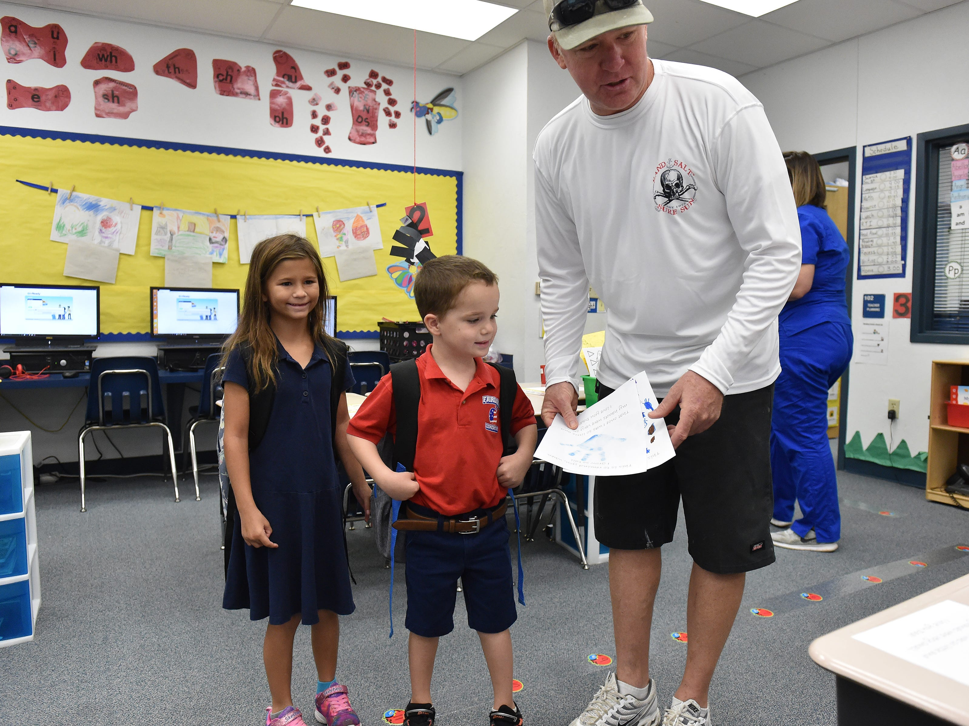 Fathers escort their children to class during Fairlawn Elementary School's 'Take your dad to school day' on Wednesday, Sept. 26, 2018, in Fort Pierce. Dozens of fathers lined up with their children outside the school to walk their kids to their classrooms, meet teachers, and sign a contract promising their commitment to their children's education.