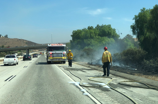 Crews work to put out a series of spot fires Wednesday on the south side of Highway 118 in Moorpark.