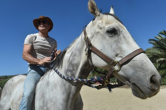 "Val Georgiev, a Simi Valley resident and thoroughbred trainer, spends time with retired racehorse Fire with Fire, one of the horses featured in the new YouTube series ""Young Gods."" Georgiev serves as the show's head wrangler and also plays a role on screen."