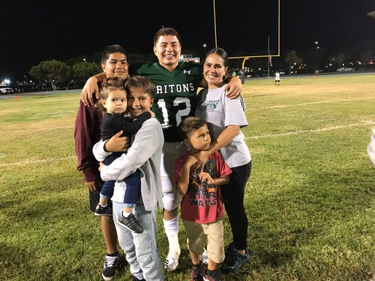 Pacifica High quarterback R.J. Maria (center) poses with his family, including his mother Vanessa (right) after the Tritons' 42-20 win over Newbury Park on Aug. 31.