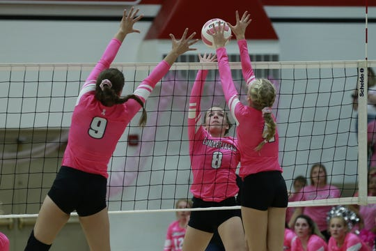 Wausau East's Gabby Braatz, middle, hits the ball while Wausau West's Tess Hauer, left, and Grace Michalske go up for a block, on Tuesday during the Volley for the Cure girls volleyball game