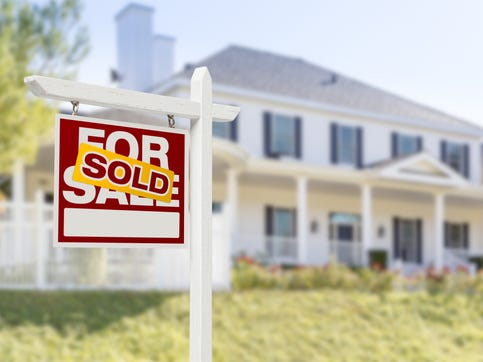 Getty Images/iStockphoto Sold Home For Sale Real Estate Sign in Front of Beautiful New House.