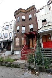 This home at 38 Oak Street in Yonkers, middle, pictured Sept. 26, 2018, cost the city $3,888.12 to clean up this neglected property.