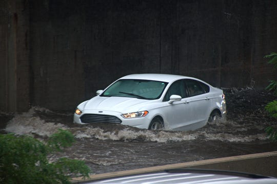 A car travels through the flooded Bronx River Parkway near Yonkers Avenue and Mount Vernon Avenue on Sept. 25, 2018.