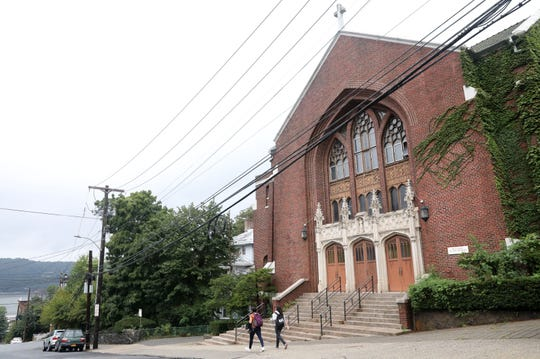 Pedestrians pass the former Our Lady of the Rosary Church in Yonkers Sept. 26, 2018 which will be renovated into a gymnasium for the Charter School of Educational Excellence. The school is expanding to include high school grades and will build a four-story building adjacent to the church.
