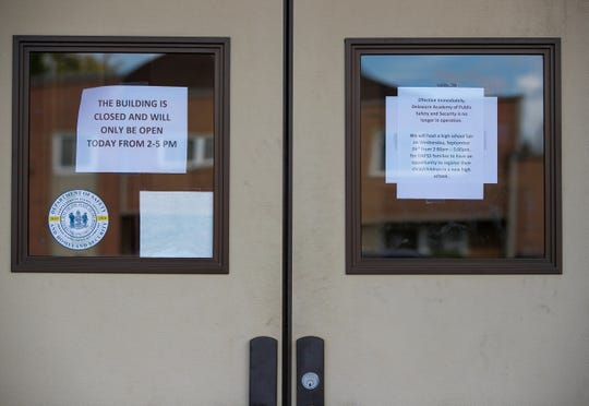 Signs posted at the Delaware Academy of Public Safety and Security where students and parents got news Tuesday night that the board will be closing the school immediately.