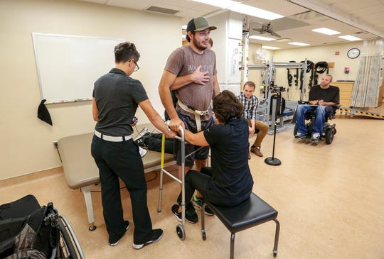 Jered Chinnock stands with the assistance of his therapy team at the Mayo Clinic in Rochester, Minn., on Sept. 18, 2018. Chinnock, paralyzed since 2013, can stand and take steps again thanks to an electrical implant that zaps his injured spine and months of intense rehab as part of a medical study at the clinic. At right is Peter Grahn, PhD, senior engineer. Second from right is doctoral candidate Jonathan Calvert. (AP Photo/Teresa Crawford)