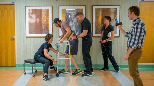 Jered Chinnock walks down a clinic hallway with his therapy team at the Mayo Clinic in Rochester, Minn. on Sept. 18, 2018. Chinnock, paralyzed since 2013, is taking steps again thanks to an electrical implant that zaps his injured spine and months of intense rehab as part of a medical study at the clinic. From left are physical therapist Megan Gill, Chinnock, kinesiologists Daniel Veith and Margaux Linde, and doctoral candidate Jonathan Calvert. (AP Photo/Teresa Crawford)