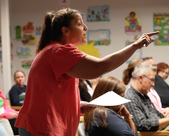 Jen Ballas, parent of students at Odyssey Charter School and a former board member, voices objection to the potential hiring of a former board president as a school administrator during a school board of directors meeting Tuesday at the Barley Mill Plaza school.