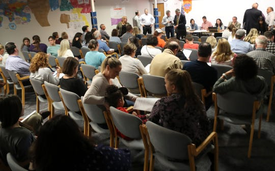 Board members and attendees gather before a board of directors meeting at Odyssey Charter School in September.