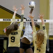 Cooper's Dazz Larkins spikes the ball past Wichita Falls Rider's Maegan Lacy, left, and Anna Grace Beasher on Tuesday at Rider. The Lady Raiders defeated the Cougars 25-17, 25-12, 25-13 in the district opener.