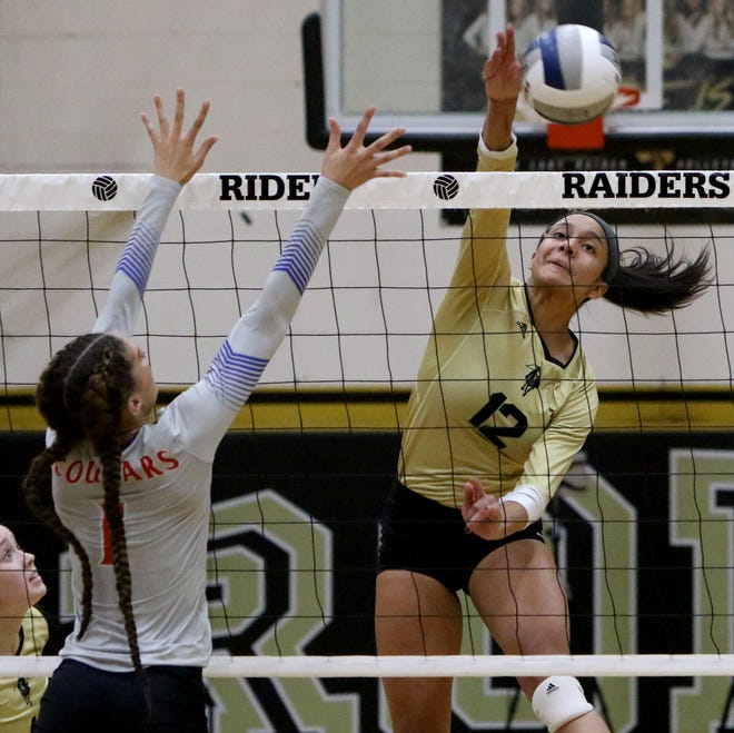 Wichita Falls Rider's Alyssa Estrada-Hamby spikes the ball as Cooper's Alexis Garcia defends during their match Tuesday at Rider. The Lady Raiders defeated the Cougars 25-17, 25-12, 25-13 in the district opener.