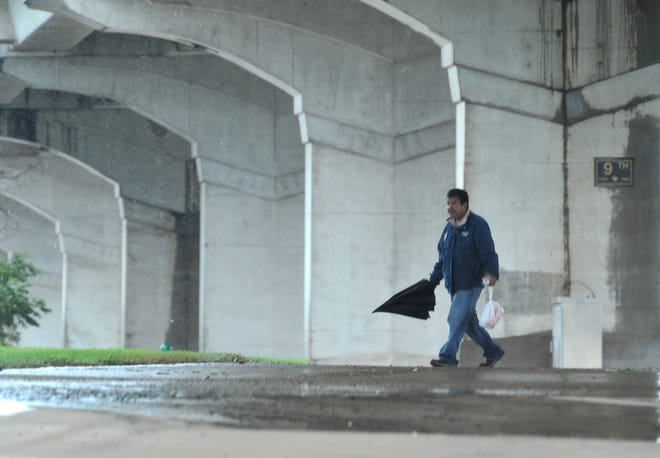 A man takes the opportunity to shake off his umbrella while walking under the Lloyd Ruby Overpass Wednesday after a cold front brought the area some rain and cooler fall-like temperatures.