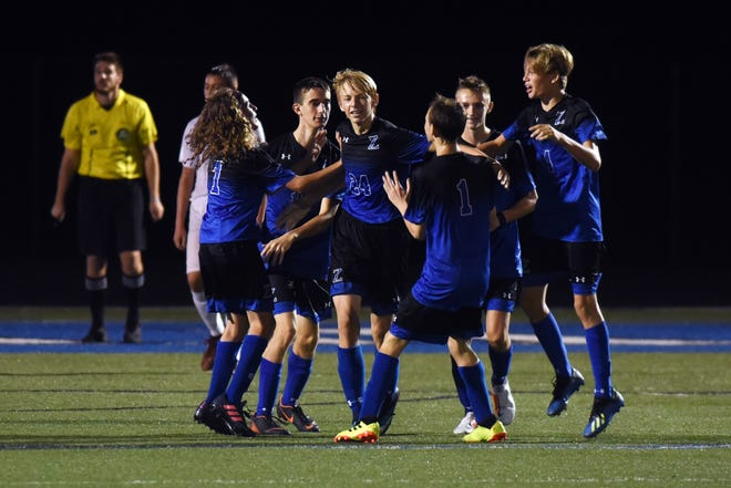 Teammates celebrate with Leyton Needles after he scored just before halftime in Zanesville's 3-1 win against Marietta on Tuesday at John D. Sulsberger Memorial Stadium.