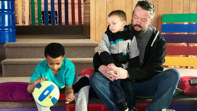 Pastor Corey Nelson sits with two children from the kids church he created.