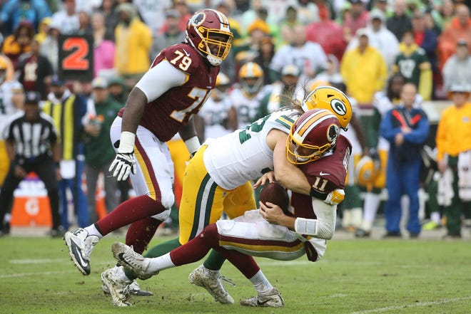 Green Bay Packers linebacker Clay Matthews (52) sacks Washington Redskins quarterback Alex Smith (11) in the third quarter at FedEx Field. Matthews received a roughing the passer penalty on the play.