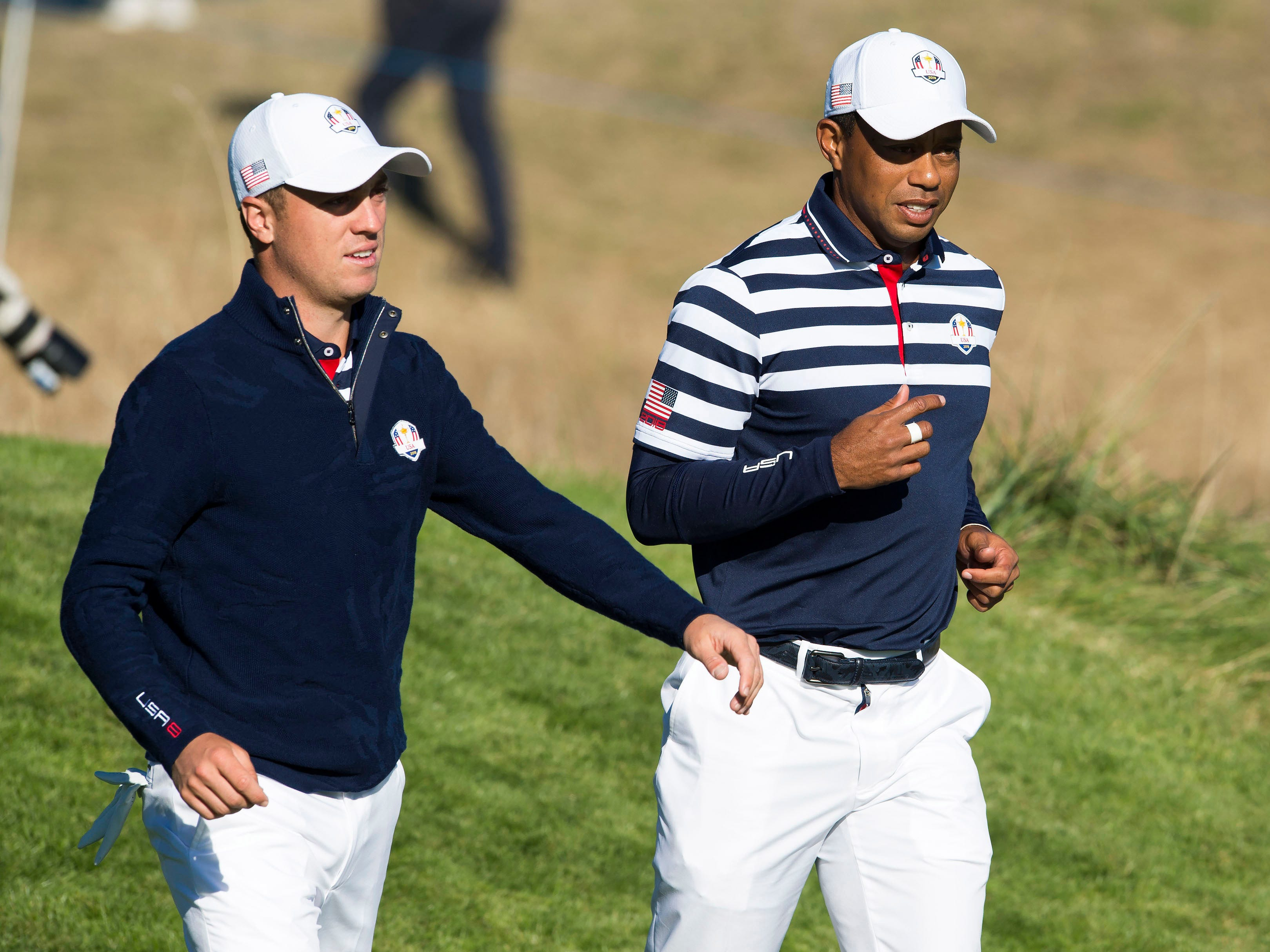Justin Thomas and Tiger Woods (right) walk from the 10th tee during a Ryder Cup practice.