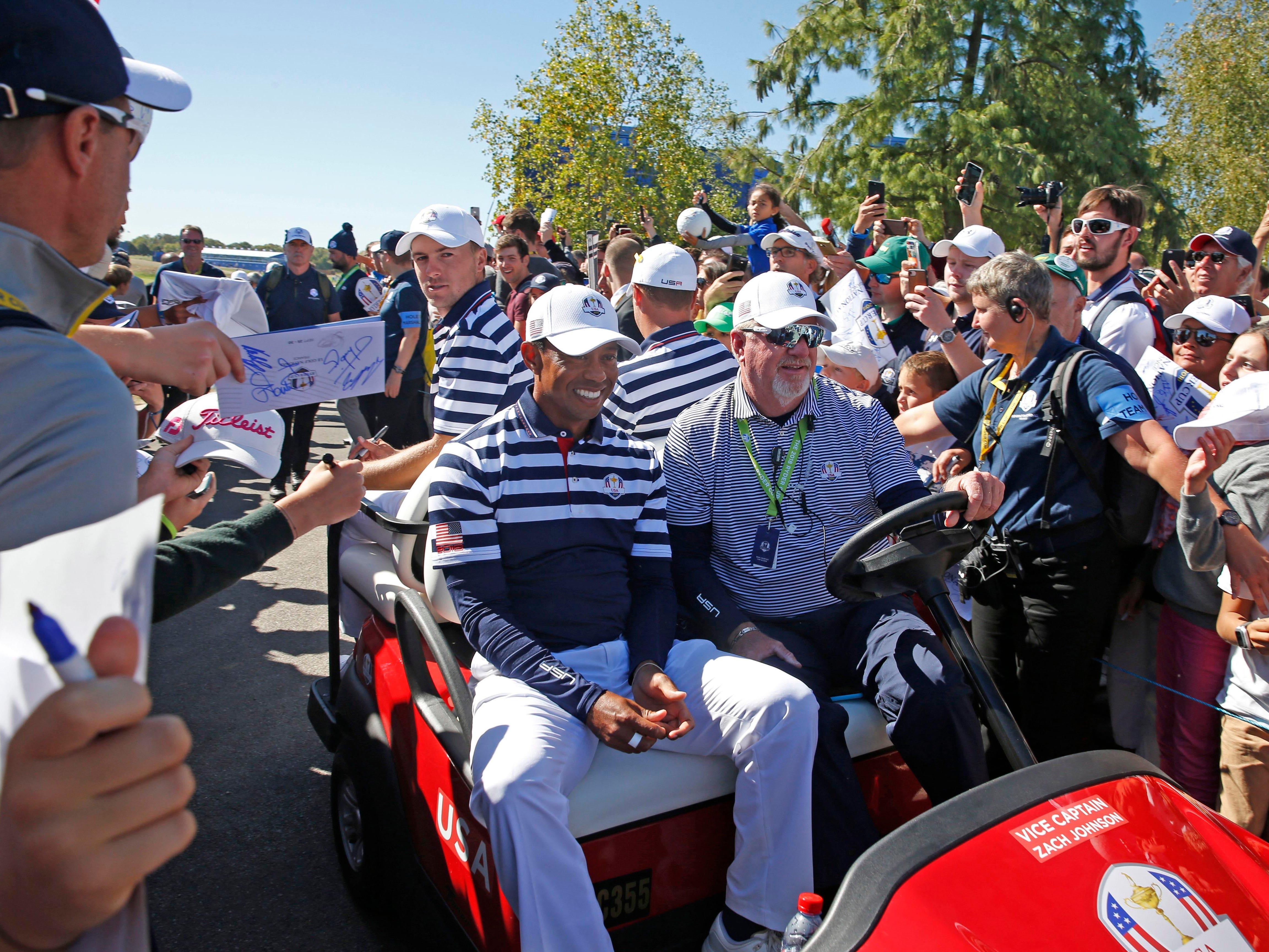 USA golfer Tiger Woods gets a ride on a golf cart to the locker room during a Ryder Cup practice round.