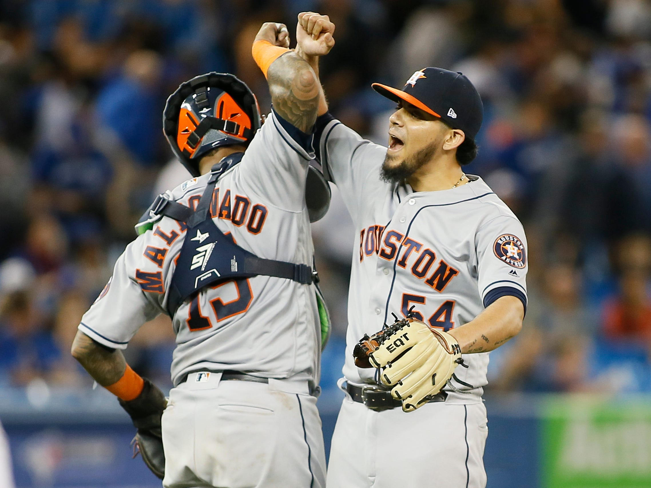 Houston Astros catcher Martin Maldonado (15) and relief pitcher Roberto Osuna (54) celebrate a win over the Toronto Blue Jays at Rogers Centre.