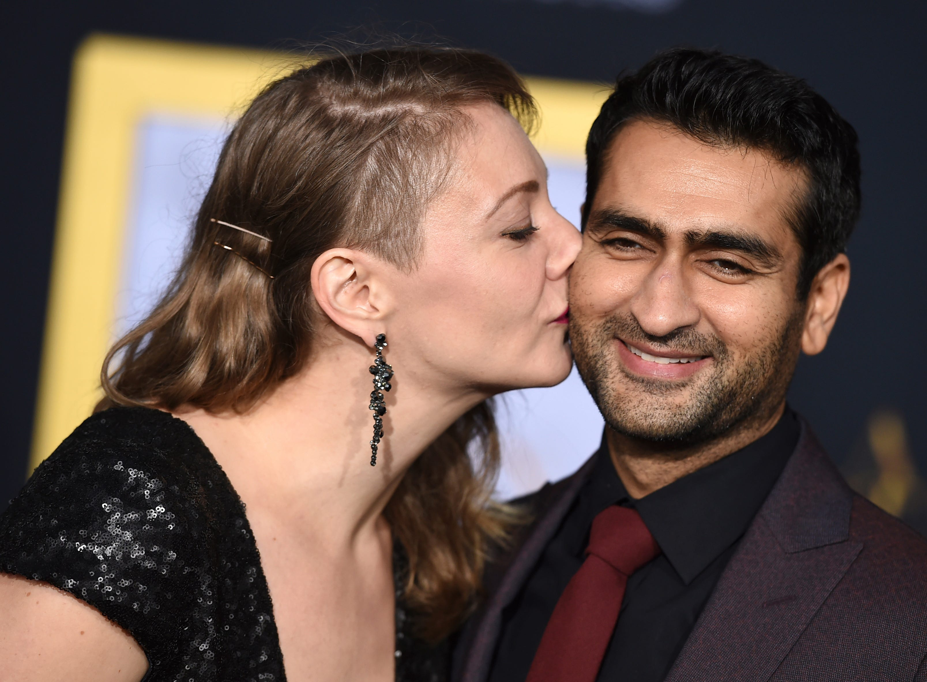 "Emily V. Gordon, left, kisses Kumail Nanjiani as they arrive at the Los Angeles premiere of ""A Star Is Born"" on Monday, Sept. 24, 2018, at the Shrine Auditorium. (Photo by Jordan Strauss/Invision/AP) ORG XMIT: CAPM164"