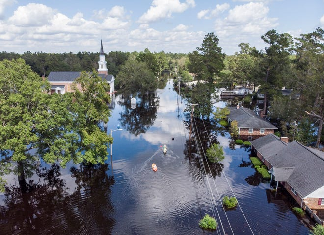 Kayaks paddle up Long Avenue past flooded sections of the Sherwood Drive community of Conway, S.C., on Sept. 23, 2018, as homes were submerged deeper than ever in floodwaters that have already set historic records.