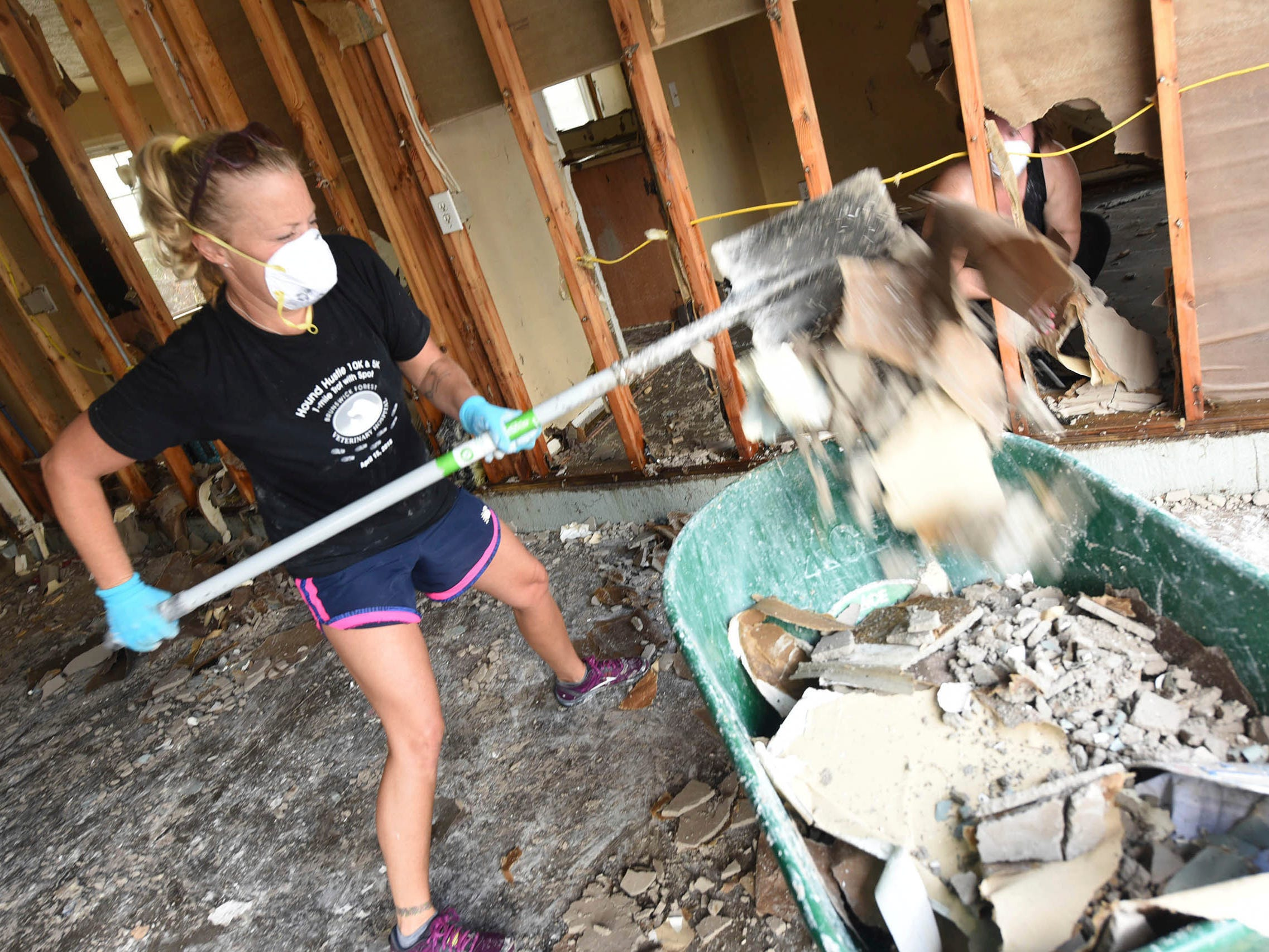 Laura Totten helps to clean out debris from a home in the Stoney Creek Plantation neighborhood on Sept. 26, 2018, in Leland, N.C.