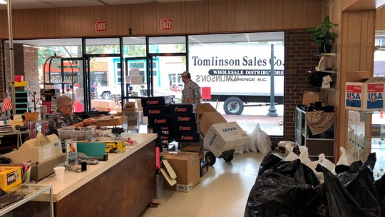 Employees at Tomlinson Department Store take all the merchandise out of the store in Georgetown, S.C., on Sept. 24, 2018. Officials have been warning of record flooding in the area from Hurricane Florence for days.
