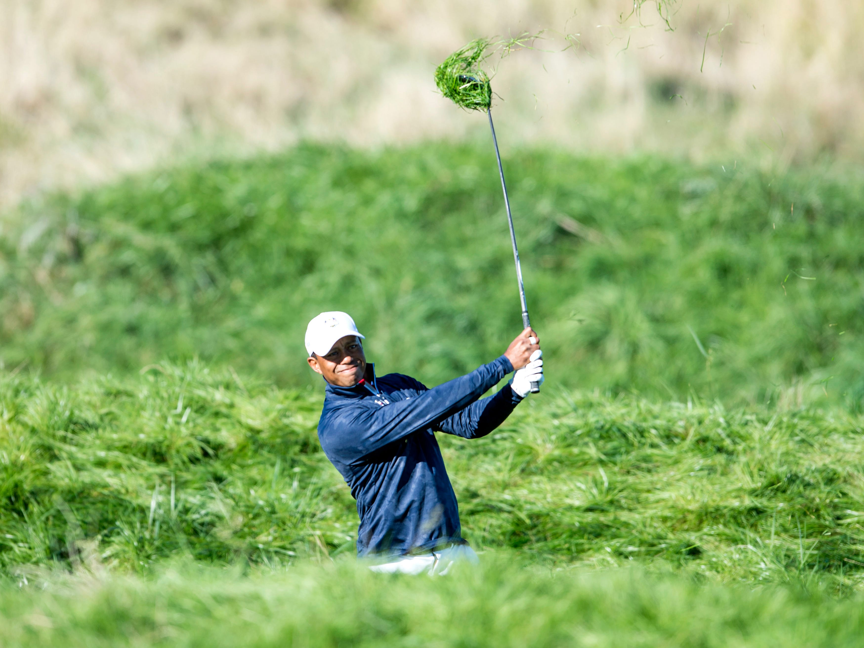 Tiger Woods plays from the rough on the 10th hole during a Ryder Cup practice round.