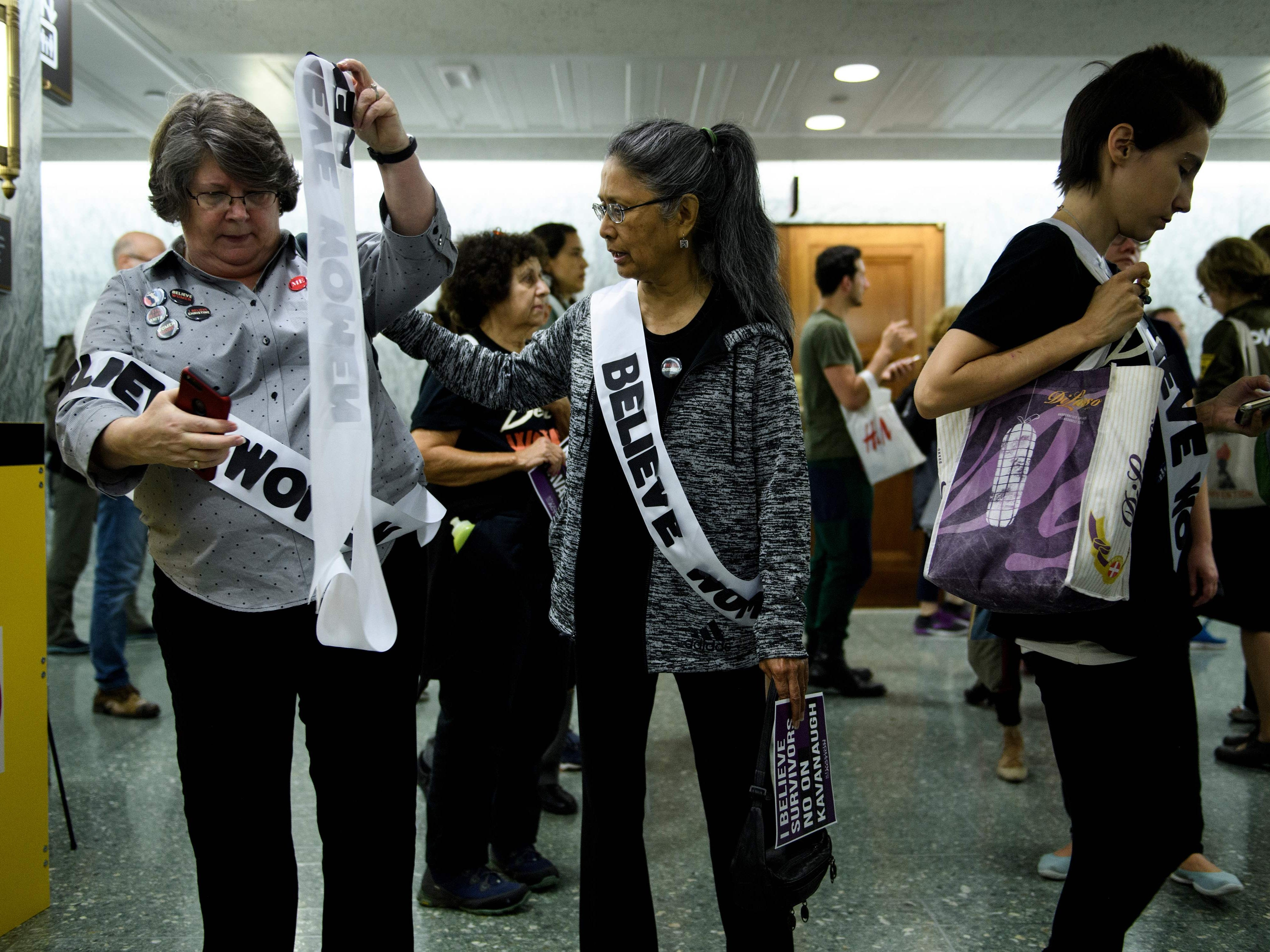 Activists walk through the halls of Dirksen Senate Office Building during protests against Judge Brett Kavanaugh on Capitol Hill September 26, 2018 in Washington, DC. - The US Senate Judiciary Committee has scheduled for Friday a preliminary vote on the nomination of Supreme Court pick Brett Kavanaugh, who is under fire over claims of sexual assault in his youth. (Photo by Brendan Smialowski / AFP)BRENDAN SMIALOWSKI/AFP/Getty Images ORIG FILE ID: AFP_19H1NL