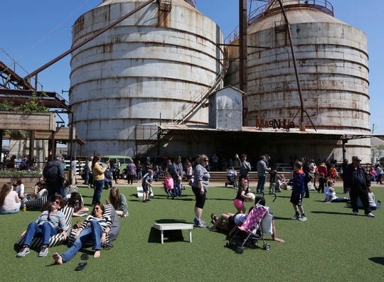 """In this March 14, 2017, photo, visitors to the Magnolia Silos stretch out on the center courtyard. TV's """"Fixer Upper"""" stars Chip and Joanna Gaines have invited the Church Under the Bridge congregation, who meet under Interstate 35, to use the lawn for their Sunday services during road construction."""