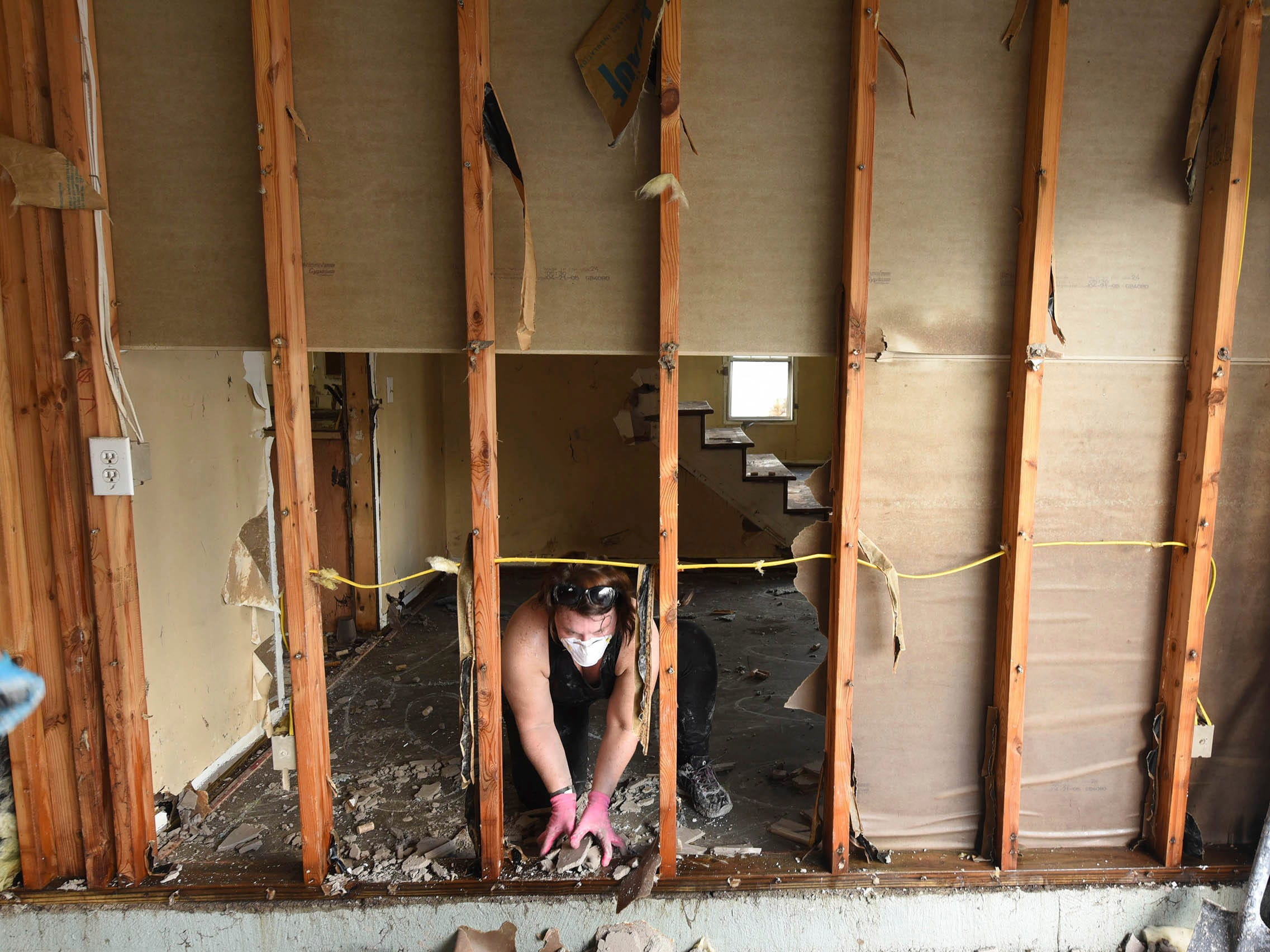 Brittany Lewis helps to clean out debris from a home in the Stoney Creek Plantation neighborhood on Sept. 26, 2018, in Leland, N.C.