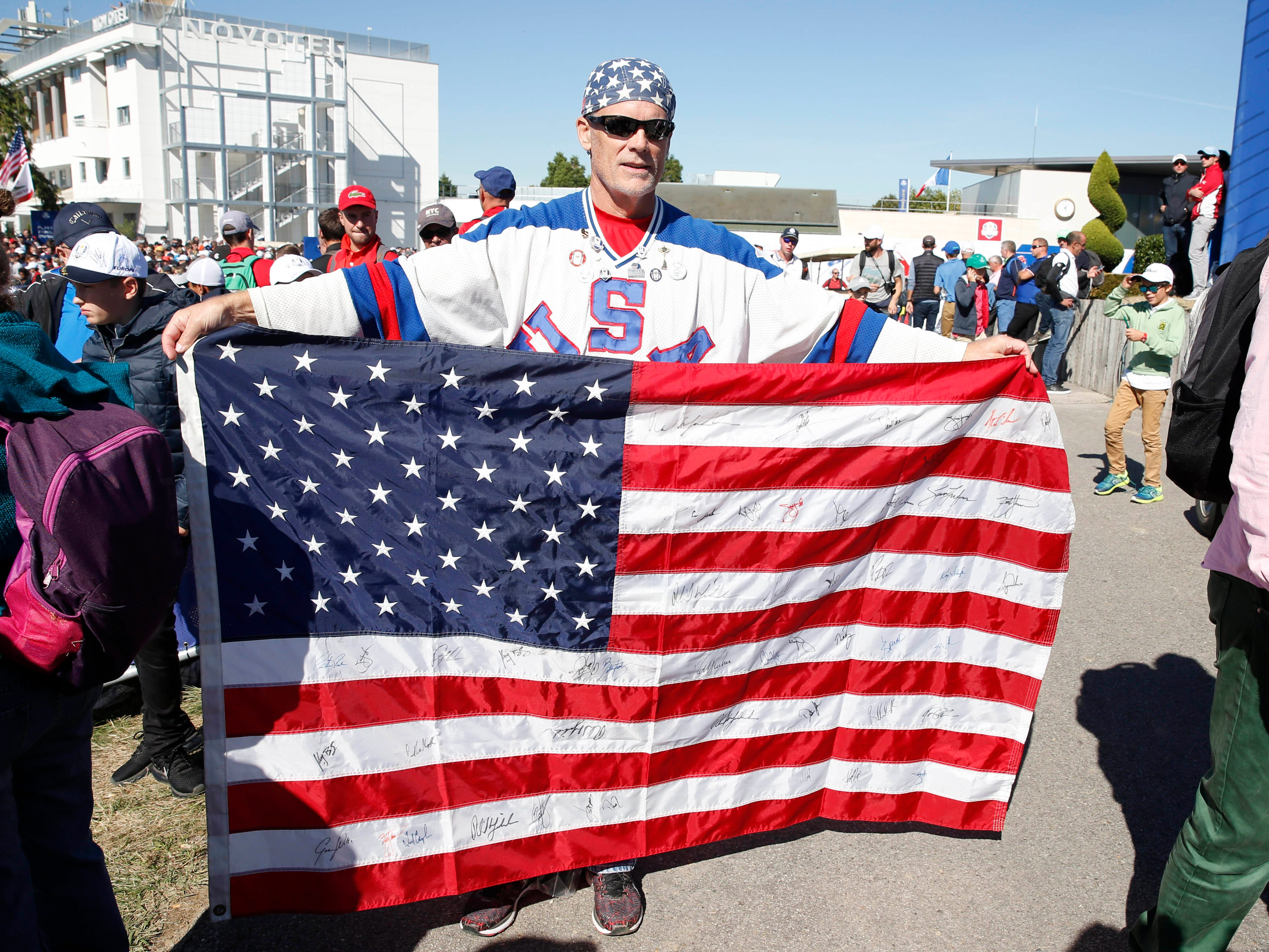 USA fan holds up an autographed flag during a Ryder Cup practice round.