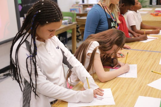 Sixth-graders Lyndsay Edwards (left)  and Alyssa Issac learn how to draw a one point perspective in art class at Pineville Elementary.