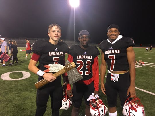 """Tioga receivers Ethan Christman (left), Deven Franklin and Kenneth Ravare pose with the """"Turnover Tomahawk"""" after the Indians' win against Bolton Sept. 20."""