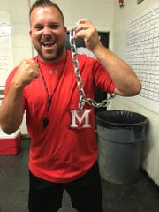 "Many coach Jess Curtis shows off the Tigers' form of the ""Turnover Chain"" before a fall scrimmage in August."