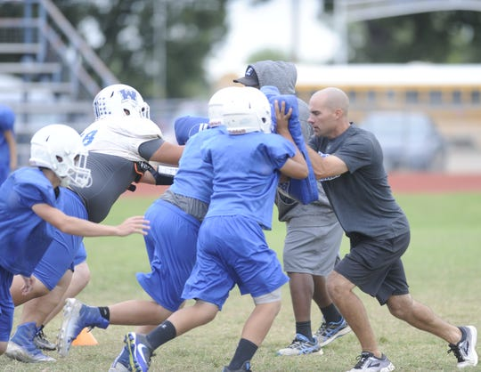 Winters coach Matt McCarty, right, helps out during an offensive drill at practice Wednesday.