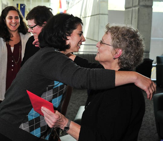 Sophia Ungert gives Merianne Miller a big hug during a reception honoring Miller on her retirement as UNCA Director of News Services in September 2012.