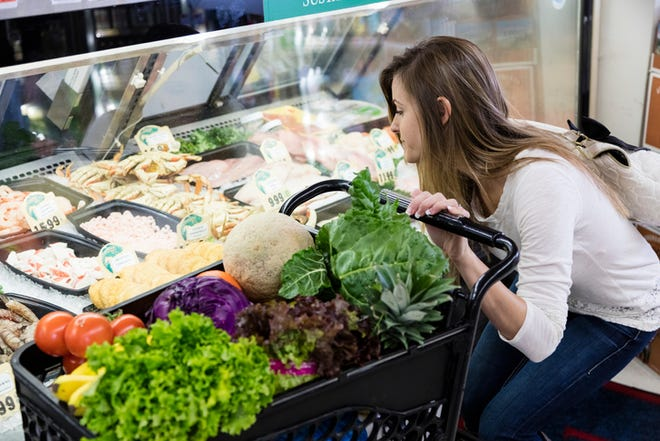 Woman shopping for groceries in meat department of grocery store