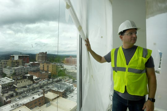 Peter Pollay, owner of Posana, pulls back a tarp to see the view from a condo at Hotel Arras Sept. 27, 2018.
